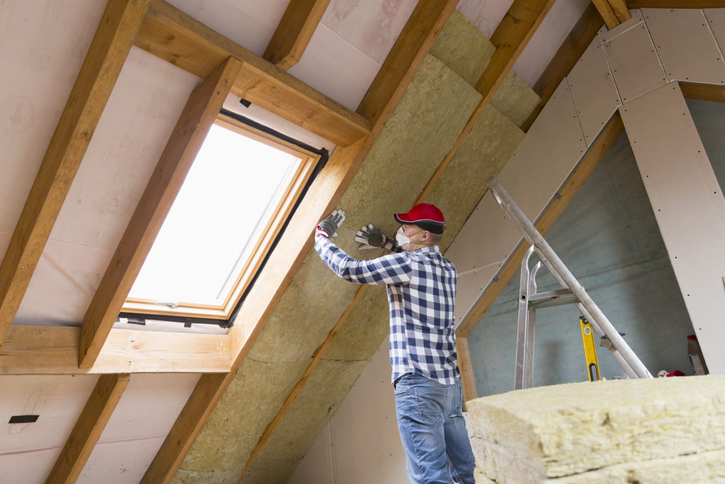 man installing attic insulation