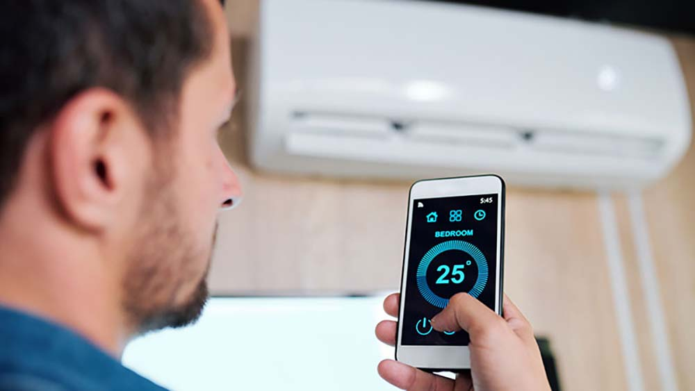 Man using smart AC app to control the AC.