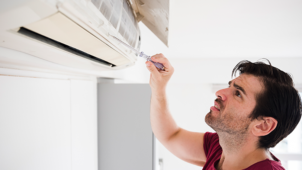 man testing ac for faults because the air conditioner smells bad