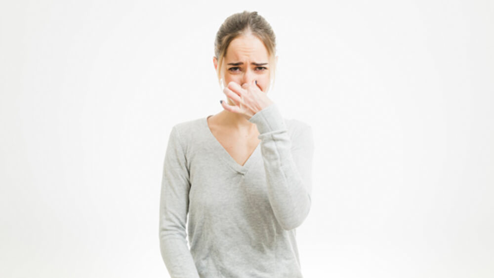 woman holding nose due to stench as its time for an AC tune up