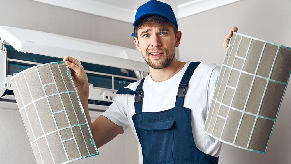 Change your AC filters in time. man showing dirty filters taken out from an air conditioner.