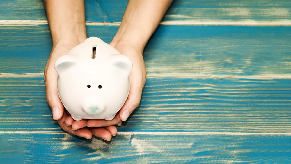 energy saving tip use less appliances. person holding piggy bank.