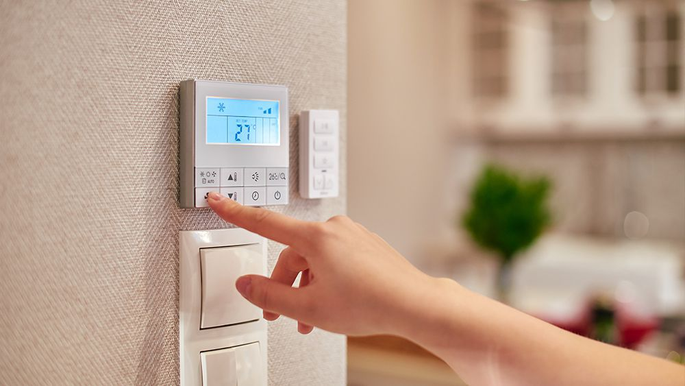 A woman using smart thermostat