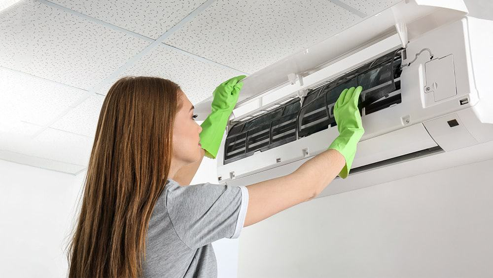 A girl cleaning air conditioner.