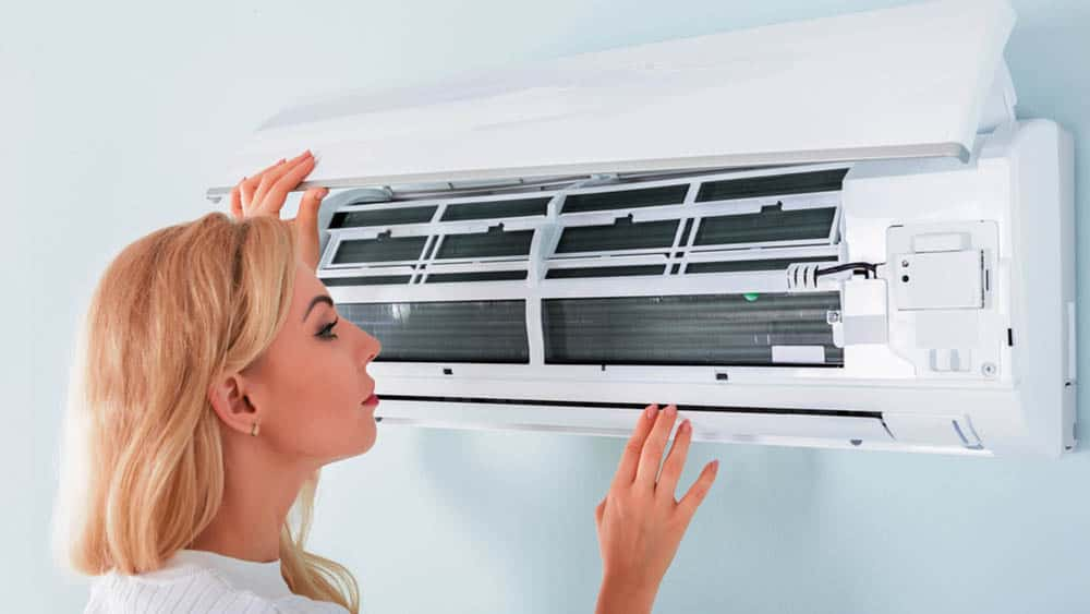 Woman checking her air conditioner.
