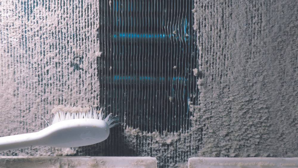 Coil cleaning using a brush