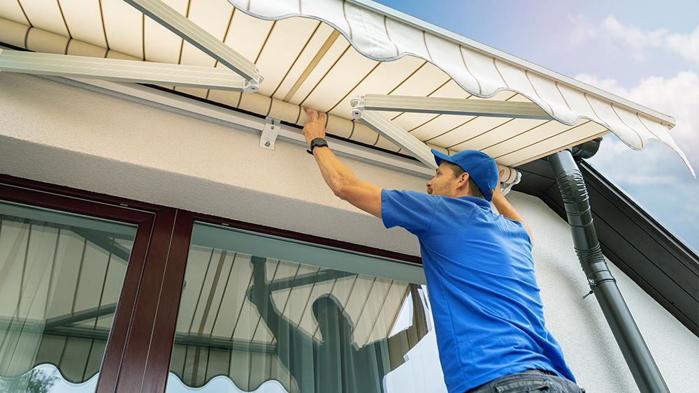 A man installing an awning to keep cool without AC