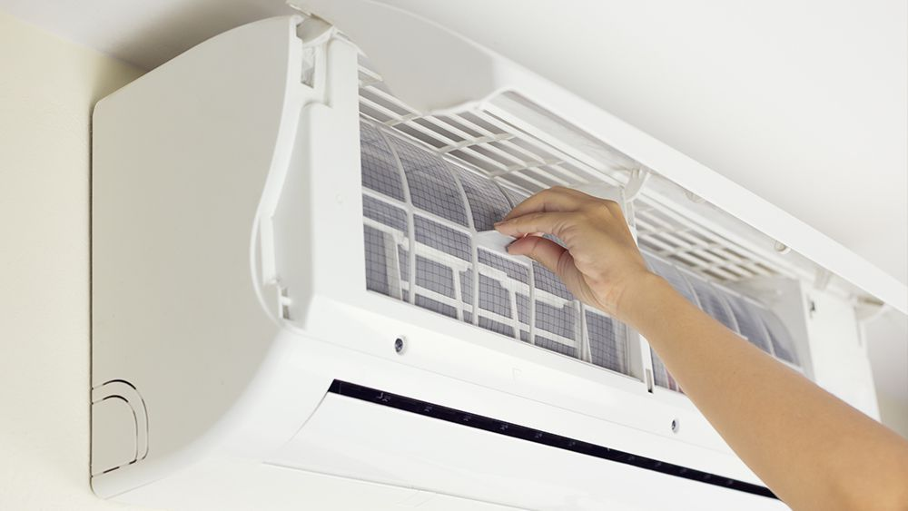 A man cleaning AC filters