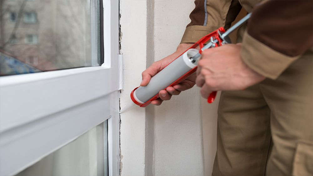 A man caulking the sides of the door