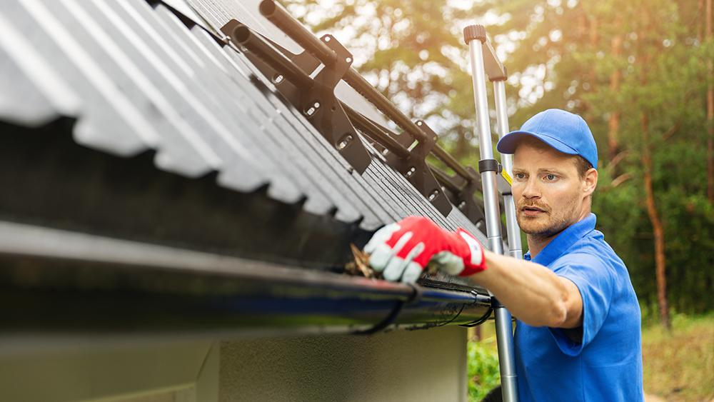 A man cleaning gutters before the onset of winter season