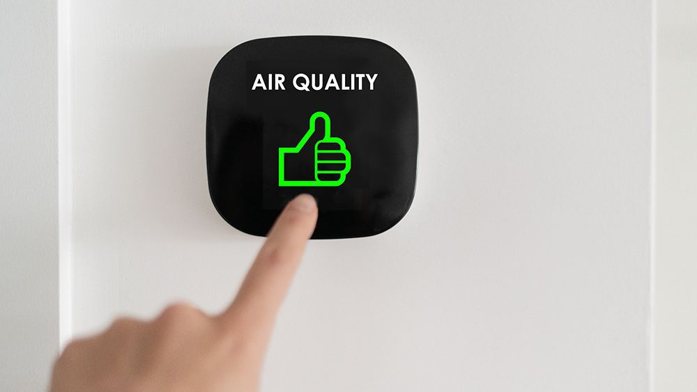 An air purifier showing that indoor air quality status is good with green thumbs up