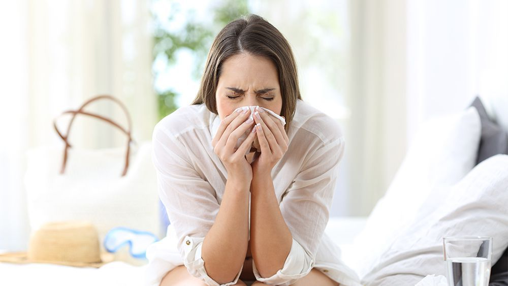 Woman having nasal allergy attack. Focusing on MERV rating is important to avoid health complications due to poor indoor air quality.