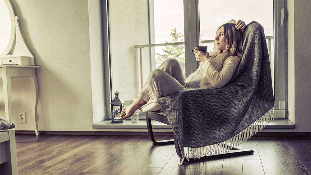 Woman relaxing with coffee in a comfy rocking chair