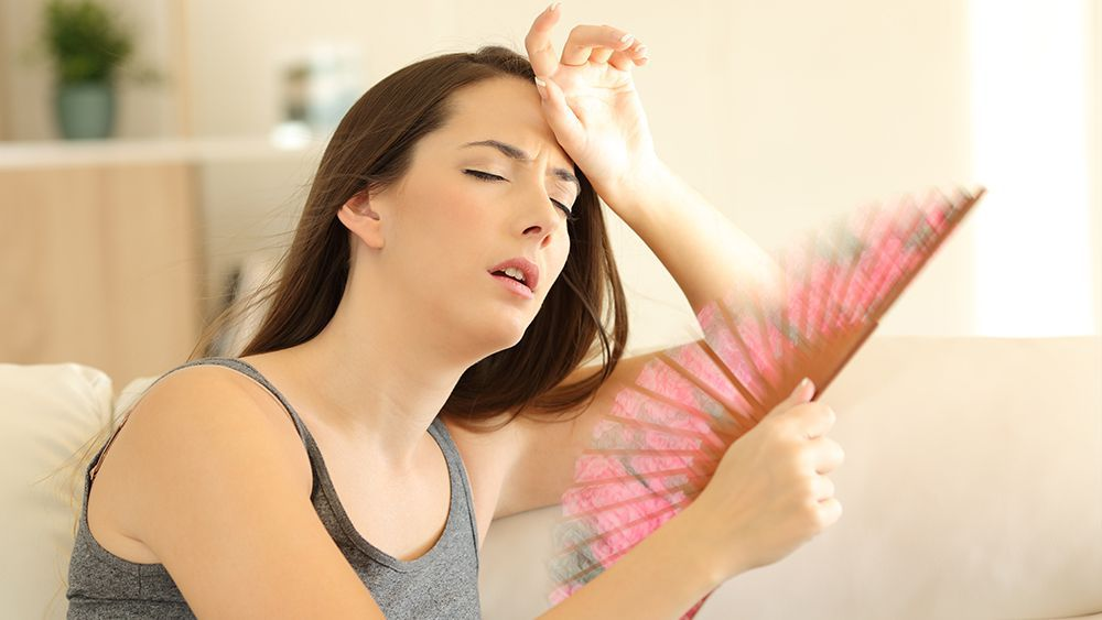 A girl is holding a fan in her hand and looking distressed due to her AC not cooling properly
