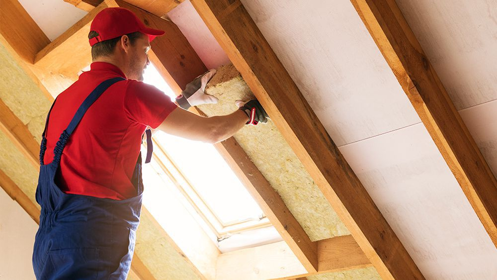A man installing roof insulation for keeping the house cool in summer