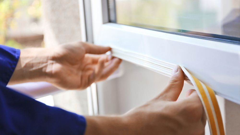 A man installing weatherstripping on the window