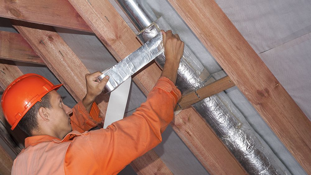 An HVAC technician insulating the the metal ducts